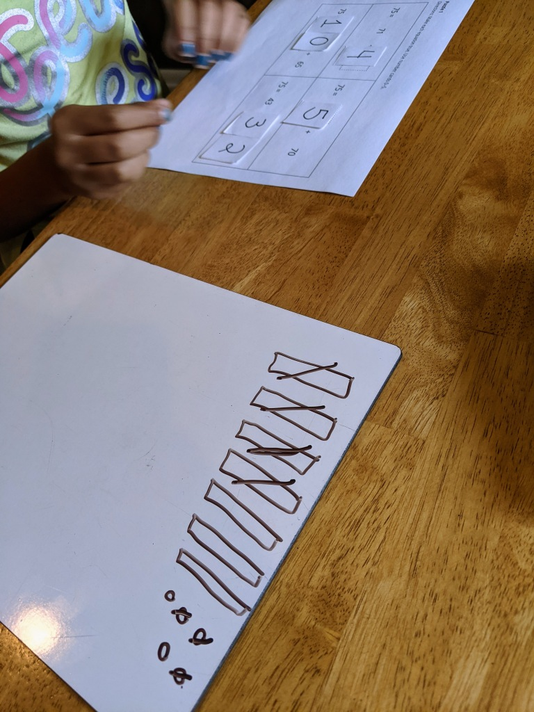 Girl with completed Number Puzzle page in front of her. Next to her is a white board showing a drawing of 75 using tens and ones. 4 tens and 3 ones are crossed out.